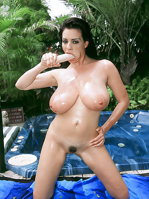 Brunette female Linsey Dawn McKenzie oils her hooters before masturbating