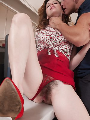 Emma Evins is joined by her man after working. He slides off her red skirt and fucks her tight hairy pussy. A hot blowjob followed by intense hard fucking of her hairy bush gets both going and his cum.