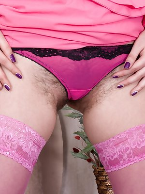 "Tayra Jane loves pink, and her pink dress matches her pink stockings and heels. It takes seconds for her to strip naked, and show off her 5'8"" all-natural figure. But, her hairy pussy steals the show."