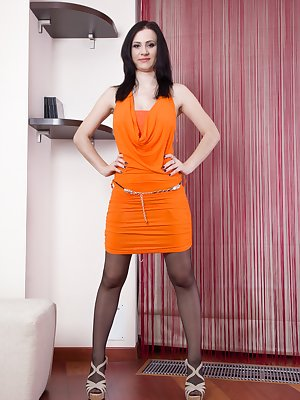Looking lovely in her orange dress, Kaira stands in her black stockings as well. A slow and sensual striptease shows off her 34D breasts and full hairy pussy, which she then shows off in bed alone.