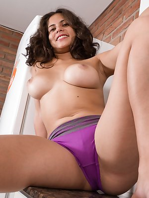 While alone in the kitchen, Sally is horny. Her colorful top and purple panties come off, and she shows off her 36C breasts and hairy pussy. She soaks her pussy with water and masturbates in there.