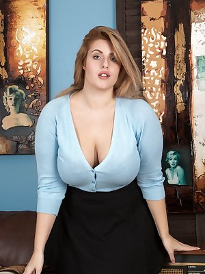 Ellie Roe stands in her blue blouse, showing off her 36F breasts and legs in her black skirt. She undoes her outfit, and her 36F breasts mix with her hairy pussy to reveal how sexy she is.
