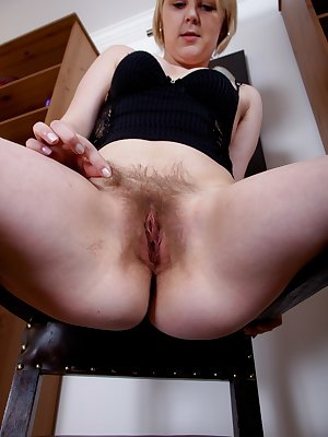 Danniella is just reading a book when she gets the urge to take off everything she is wearing and get on the floor to admire her hairy pussy. She tugs on the hairs and spreads her legs wide open.