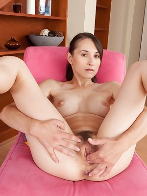Standing near the staircase, Jennifer Tate sticks her ass up in the air as she bends over a chair. It feels so good she takes off her panties and clothes and sticks a vibrator in her hairy pussy.