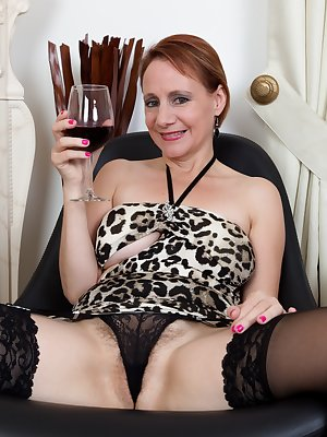 Tiffany T. sips her glass of beverage in front of the fireplace and slides her cheetah dress all the way up. Her hairy pussy pops out of her sexy panties. And then she plays with her hairy pussy.