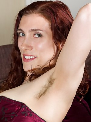 Hairy girl Amanda sits on her couch. She spreads her legs, tufts of pussy hair visible even though she's still wearing underwear. The beautiful redhead strips and teases her pussy.