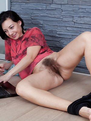 Eva loves to watch porn while she touches that hairy masterpiece between her legs. She's so hairy that her bush pops out of all sides of her panties with curly brown hairs.