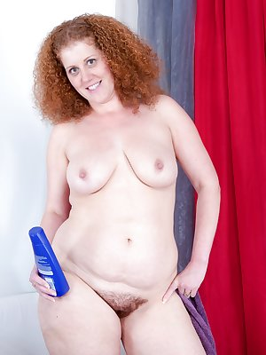 Hairy girl Francesca May appears in a sumptuous purple towel. the redhead blows a kiss, then gets on all fours, showing her red, hairy bush. Her pussy lips push through her thick hair.