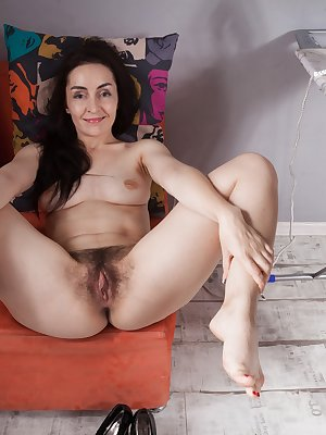 Di Devi is modeling her red lingerie and showing off her hairy pits and pussy too. She strips nude, and spreads her legs to show off her natural body. She is 34, sexy, and quite hairy to see.