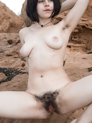 Ole Nina is outdoors by the rocks and water, and feeling horny. She finds a spot, strips nude on the rocks and has fun. She has fun showing off her hairy pits and hairy bush outdoors and in the sun.