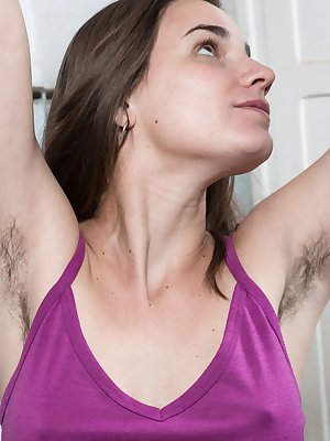 Natalia is in her kitchen showing off her hairy pits early. She slides off her purple top and denim shorts, and has a totally naturally hairy body. She gets on her counter and bends over to show it all.