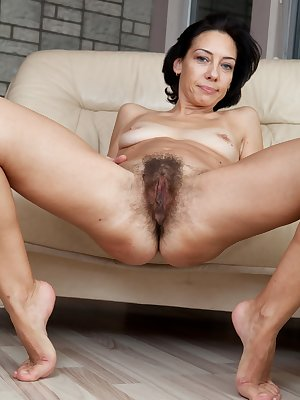 Eva's panties can't contain her massive bush. This hairy woman has penetrating blue eyes and a thin body. She pulls on her pussy hair and spreads her labia wide open to show her pink.