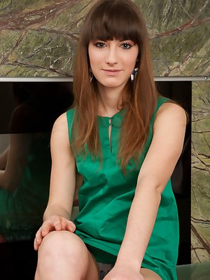 Gorgeous Natasha strips out of her sexy green dress and shows off her hairy assets in front of the fireplace.