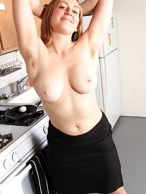 Left wearing only a apron, horny Jessica teases and spreads her wonderful hairy pussy on the kitchen bench.