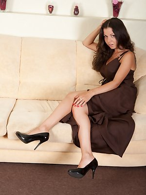 See this beautiful hairy vixen climb out of her sexy cocktail dress and vigorously tease her furry pussy lips with her fingers on the sofa