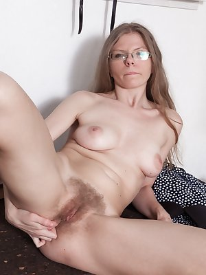 Ekaterina Ananasova sits at her desk reading and showing off her panties up her skirt. She strips nude and strokes her hairy pussy a lot. She finishes by masturbating and orgasming at her desk.