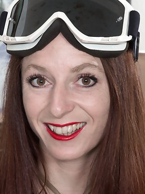 Evane Nordstern is loving her ski goggles and striped outfit. She takes the outfit off and sits naked on her couch. She moves to the carpet where her hairy pussy shines and so does her petite body.