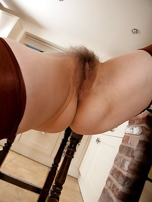 Sexy mature Hazel gets turned on in the kitchen and decides to give her soft curvy body and big hairy pussy some air.