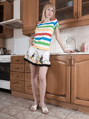 """Natinella is relaxing in her kitchen and showing off her 5'4"""" petite body. She strips naked and her slender figure sits on her counter. There, she shows off her hairy pussy and pink pussy lips."""