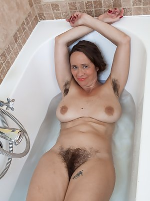 Josie is taking a bath and wearing her white top and panties before getting in. She strips nude and gets in the water. Her hairy pussy gets wet and she touches her hairy bush while enjoying the tub.