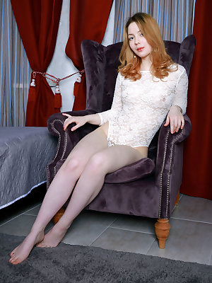 Natural redhead slips off her onesie to model naked on a velvet chair