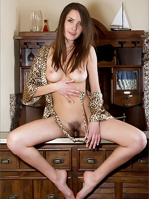 Pretty brunette with nice tits spreading on the dresser to display hairy muff
