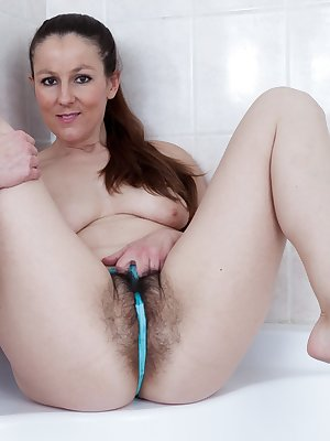 Valentina Ross is ready for her shower, and takes off her pink robe and blue panties, covering her hairy pussy. Feeling horny, she gets her glass dildo and masturbates there and loves it all.