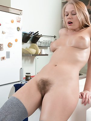 White enjoying a salad, Darina Nikitina takes off her blue dress and grey stockings. While near the table, she starts to orgasm with fingers sliding in and out of her hairy pussy, orgasming from it.