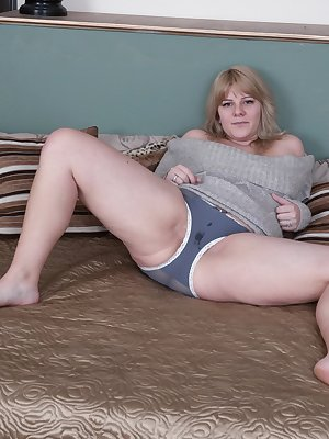 Jodie Dallas is laying in bed in her grey sweater, feeling horny. The sweater and panties come off and she shows off her naturally hairy pussy. She spreads her legs wide and is wet from feeling horny.