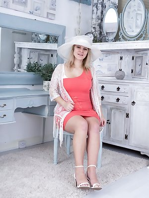 Jodie Dallas is showing off her white hat and her pink dress. As she undresses, she has her 34B breasts and hairy bush flowing. She poses with glamour and looks sensual with her naturally hairy body.