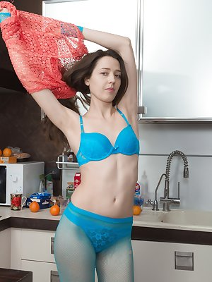 Lisa Carry has tight blue tights on in her kitchen, and slides them off with her blue lingerie. All naked, she gets on her counter and spreads her legs to show the camera her hairy pussy.