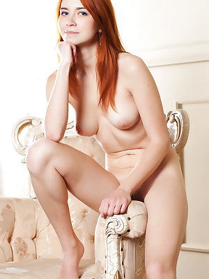 Naked redhead spreads her long legs open for a view of her hairy pussy
