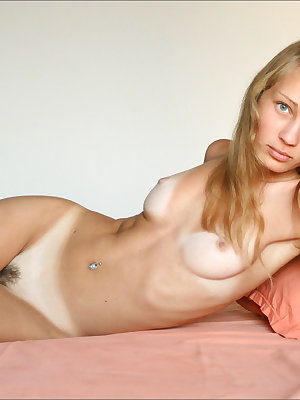 Blue eyed cutie rolls around naked on her bed to show her soft ass closeup