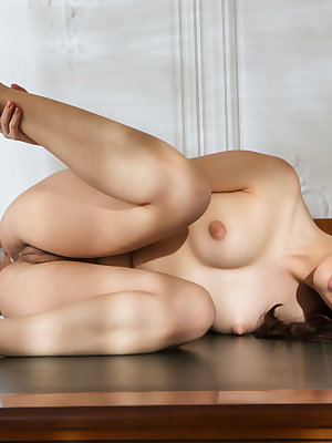 Nude solo girl Shania flaunts her all natural pussy on top of a wooden desk