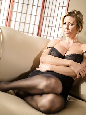 Busty blonde in hot lingerie & black stockings striping & spreading long legs