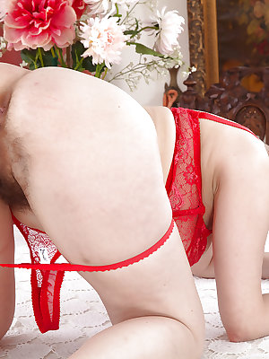 Older woman Nikita slips off red lace panties for hairy pussy exposure
