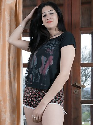 Francesca is wearing her black top and floral shorts by her new armchair. As she strips, her nipples are hard and her pussy is hairy. She touches her wet pussy all over and bends over to show it more.