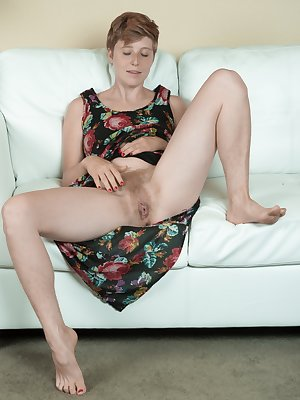 Aurora Odaire is enjoying beverage on her white sofa and having fun. She strips off the floral dress and sits naked on her sofa. She has hairy pits and a hairy pussy, and then lays naked on her floor.