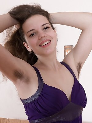 Fiorella is in her purple dress and showing off her hairy pits early. She strips completely naked on her brown couch and displays her body. She then touches her hairy bush and pink pussy lips.