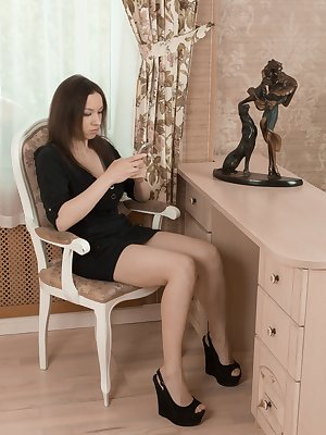 Veronika Mars sits in her black dress and loves her phone. She strips naked on her chair, and has E cup breasts and a very full hairy pussy. She touches her pink pussy and bush on the chair.