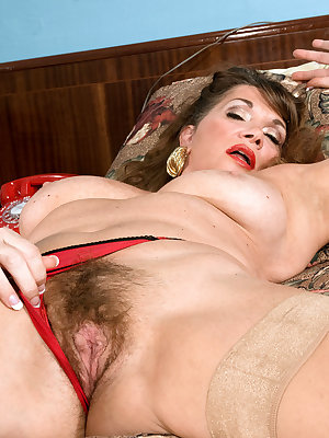Older lady Josette Lynn undresses before toying her hairy muff on her bed