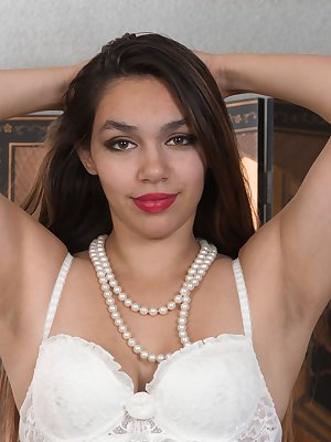 Victoria Marie is showing off her figure in her white dress and pink panties on her red couch. She elegantly strips naked there, licks her nipples, and then drags pearls across her hairy pussy.