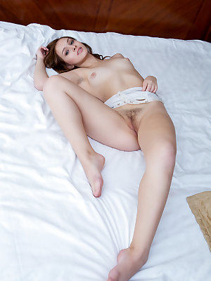 Barely legal solo girl Demetra gets naked atop her white bed sheets