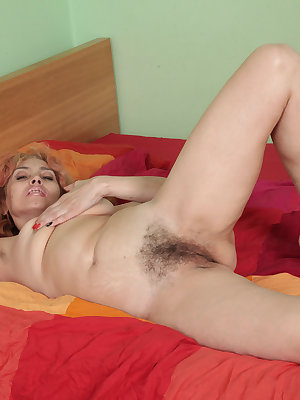 Hirsute mature woman Karolina doffs black lingerie to display her beaver