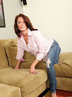 Mature woman Mimi Moore slips her ripped jeans off as she gets naked