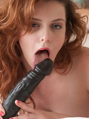 Redhead amateur Emma Evins peels off her nylons before toying her beaver