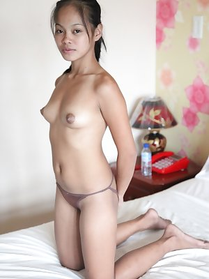 Young Asian girl bares her small tits as she undresses for a sex tourist