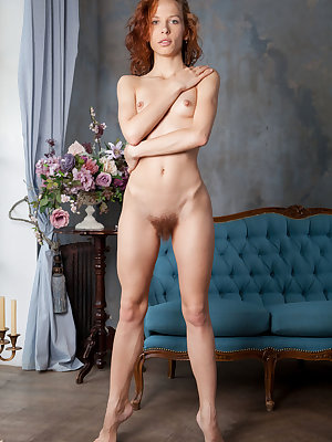 Delicious redhead Dennie playing with her furry muff on the sofa