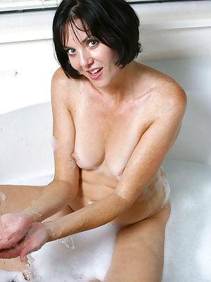 Short haired older lady attends to her horny bush in the bathtub