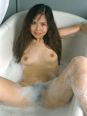 Wet Asian first timer displaying hairy pussy and tight ass in bathtub